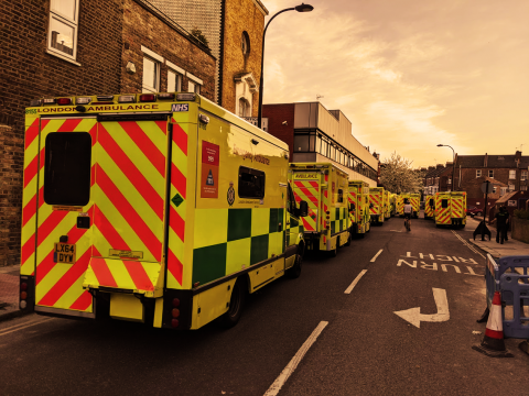 line of London Ambulance Service ambulance trucks on a residential road