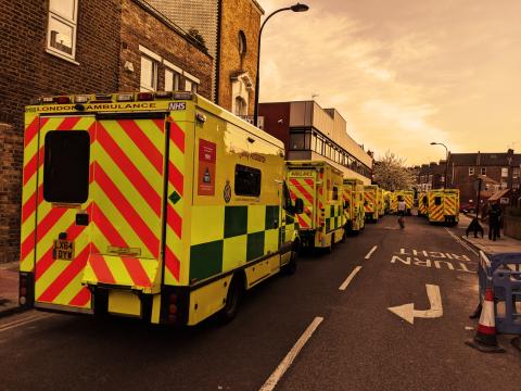 line of London Ambulance Service ambulance trucks on a residential road